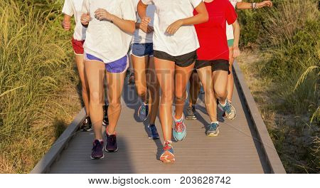 A high school girls cross country team running as a group on the boardwalk from the Fire Island Lighthouse with beach grass all around them.