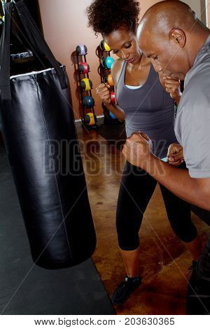 Man training his client in kick boxing.