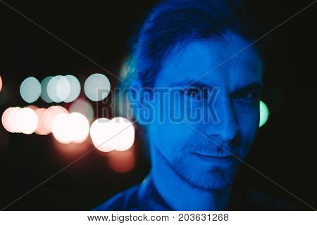 Cute young man with a beard on his face who falls blue light. Photo at night.