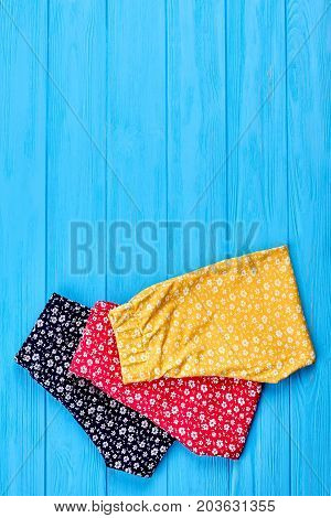 Natural baby clothing and copy space. Top view of new folded baby girl summer trousers on sale. Summer childs clothes in vintage print.
