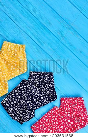 Top view of modern leggins for kids. Collection of colored summer pants in vintage print for little girl, copy space.