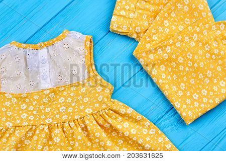 Close up of natural outfit for baby-girl. Yellow textile summer suit for little girls on wooden background. Pants and dress in vintage print for baby-girl for casual wear.
