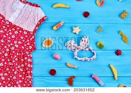 Summer kids wear, sweets and head wrap. Red small girls dress with pattern of white flowers, hairband, sweets, blue wooden background.