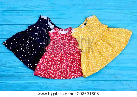 Collection of newborn colorful dresses. Vintage print cotton dresses of infant girls for casual wear. Setting of summer sleeveless dresses for baby-girls.