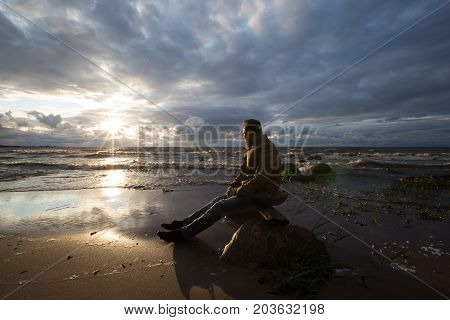bearded guy sitting on the beach at sunset