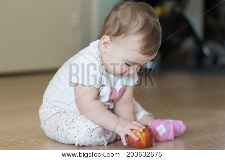 Little child sitting at home on the floor with a red apple.