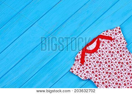 Infant girl apparel, copy space. Vintage print baby girl bodysuit on blue wooden background. Patterned infant baby girl garment.