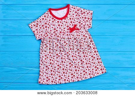 Toddler girl cute cotton dress. Infant girl natural summer gown on blue wooden background. Baby girl summer outfit.