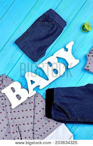 Top view of baby-boy fashion clothes. Word baby and kids garment for autumn wear. Setting of high quality clothes for infant boys.