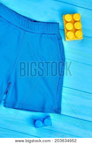 Baby-boy cotton shorts, top view. High quality casual shorts for toddler boy, blue wooden background. Textile clothes for kids.