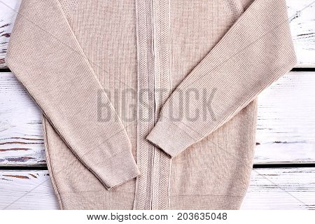 Cropped image of warm knitted sweater. New knitwear for children close up. Classic beige knitted jacket for boys.