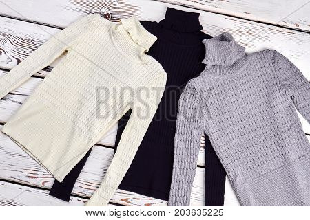 Collection of high quality turtleneck sweaters. Three knitted colored winter sweaters for children, top view.