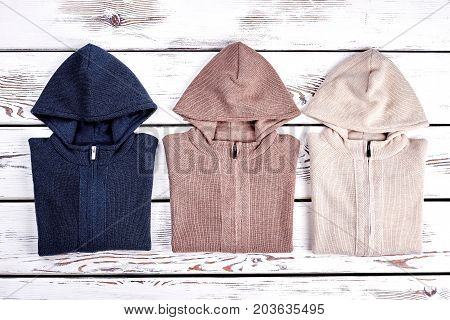 Collection of new knitted hooded sweaters. Beautifully folded colored knit hoodie pullovers for childrens on sale. High quality hooded kids jackets for casual wear.