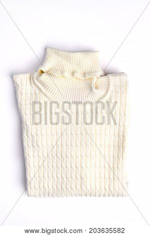 White warm folded winter sweater. Knitted sweater with a beautiful ornament. Beautifully folded sweater isolated on white background.
