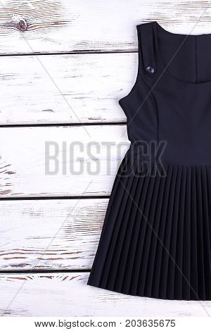 Girls black pleated dress for school. Classic black school uniform dress for girls on wooden background. Childrens school outfit.