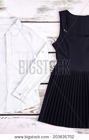 Classic girls blouse and dress for school. White long sleeve cotton frill blouse for girls, black dress. Girls school uniform.