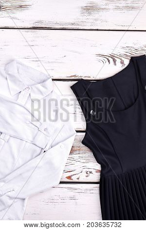 White blouse and black dress for school girl. Girls pretty white shirt and black pleated dress on wooden background. Little girls school uniform on sale.