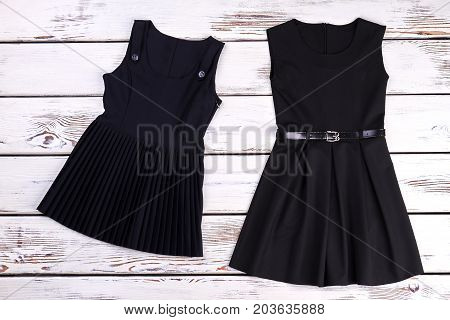 Two black dresses, wooden background. A-line dress and pleated girls dress for school wear. Girls school clothes.