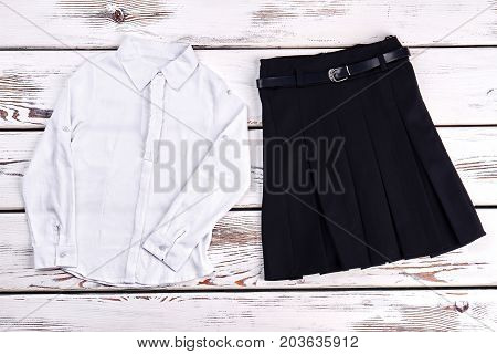 Girls school uniform, top view. White cotton shirt and black pleated skirt for school wear, old wooden background. Girls formal school outfit.