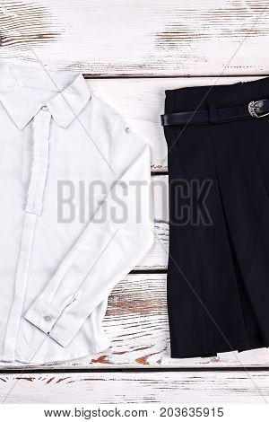 Classic white shirt and black skirt. Cotton white long sleeve blouse with collar and black pleated skirt with belt. Collection of new school uniform for girls.