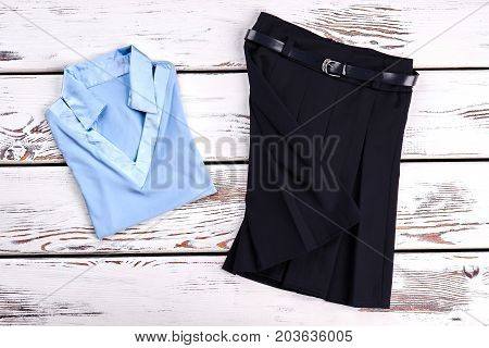 Beautiful set of school clothes for girl. New light blue girls blouse and black pleated skirt for school wear, old wooden background.