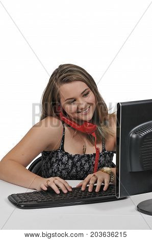 Woman executive or manager using a desktop computer and a landline phone