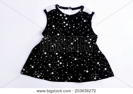 Baby-girl black printed dress. Infant girl cotton black dress with a pattern of small white stars, isolated on white background.