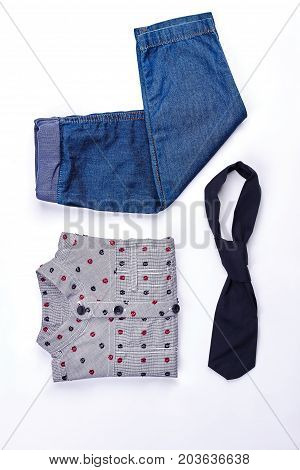 Little boys fashion clothes background. Infant boy denim jeans, shirt and tie on white background. New fashion clothes for toddler boys.