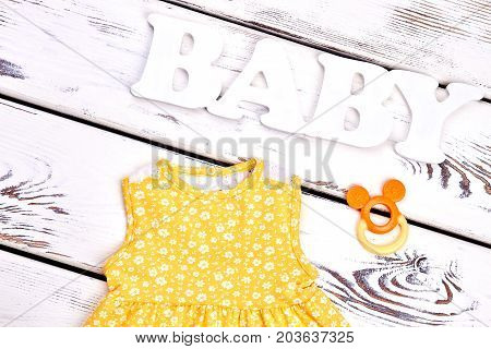 Baby-girl boutique clothes, accessories. Infant girl new cotton sundress, teether, old wooden background, top view. Kids clothing on sale.