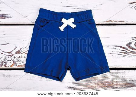 Baby boy dark blue cotton shorts. Childrens summer shorts on white wooden background. Brand kids apparel on sale.