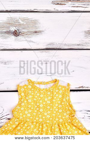 Baby-girl patterned dress. Kids beautiful yellow sundress with a pattern of small white flowers, copy space.