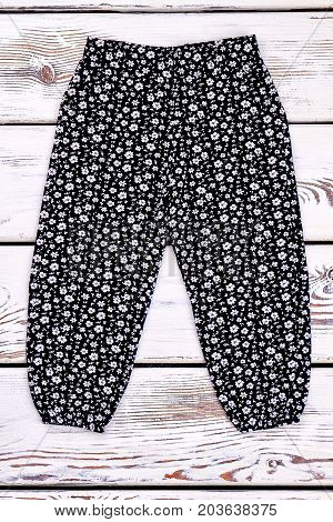 Toddler girl black printed trousers. Baby-girl flower print long pants on white wooden background. Kids brand garment on sale.