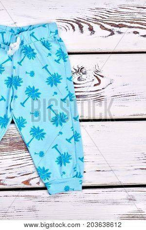 Baby-girl blue patterned harems. Toddler girl blue pants with a pattern of palm tree, wooden background, top view. Kids summer fashion style.