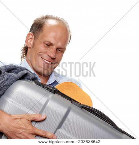 Young man traveler trying to close valise full of clothes