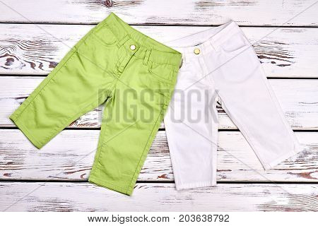 Set of high quality kids trousers. New collection of summer trousers for childrens, old wooden background. Kids boutique outfit.
