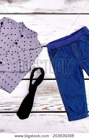 Baby boy stylish autumn garment. Toddler boy brand clothes on white wooden background, top view. Kids fashion style.