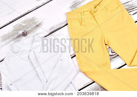 Girls high quality cotton garment. Teen girl beautiful long sleeve blouse, yellow skinny pants on wooden background. Childrens clothes on sale.