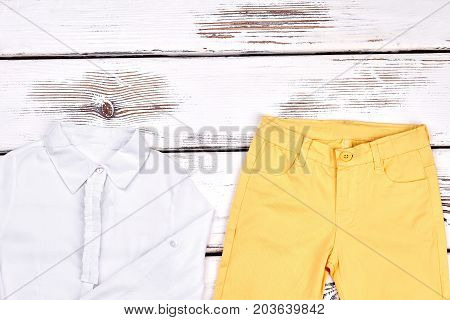 Teenage girls elegant outfit. Young girl white blouse and skinny colored trousers on white wooden background. Girls classic outfit.