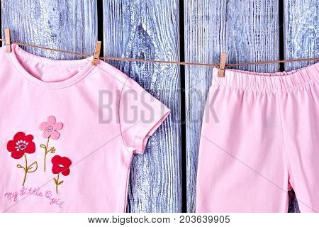 Infant girl clothes hanging on rope. Toddler girl casual apparel drying on rope on wooden background.