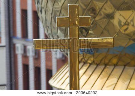 Golden orthodox cross on dome of church, telephoto shot