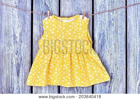 Toddler girls yellow top on rope. Baby-girl beautiful dress hanging on clothesline on grey wooden background.