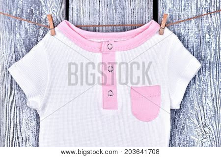 Kids beautiful t-shirt on rope. Infant girl organic bodysuit drying on clothesline on old wooden background. Kids apparel in laundry.