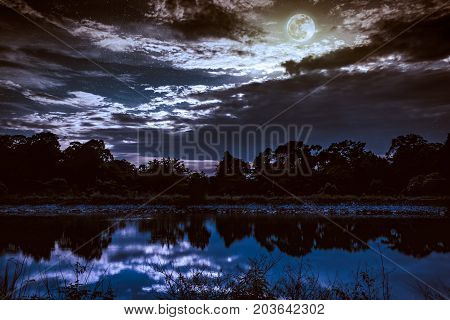 Sky With Many Star And Full Moon Above Silhouettes Of Trees And Lake.