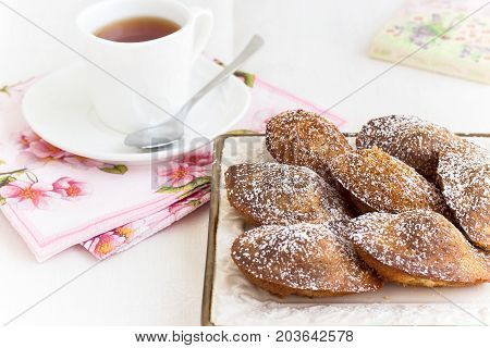 Orange Chocolate French Cookies Madeleine Shell Form And Tea In White Cup. Close Up. White Backgroun