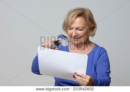 Smiling Elderly Woman Using A Magnifying Glass