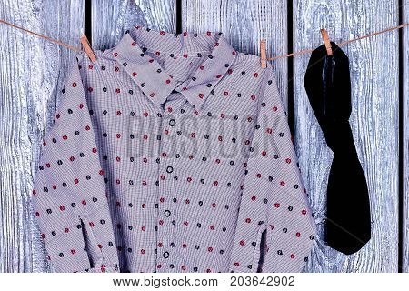 Boys garment hanging on rope. Clothesline with hanging baby boy clothes on wooden background close up.