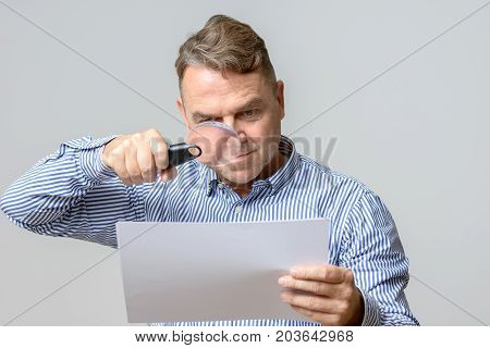 Middle Aged Man Using A Magnifying Glass