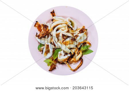 Grilled Squid with Salt and basil from top-view Thai food. Squid tentacles and garlic saute on dish isolated on white background.