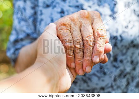 Close up elderly female's shaking hand held by young carer's hands outdoor