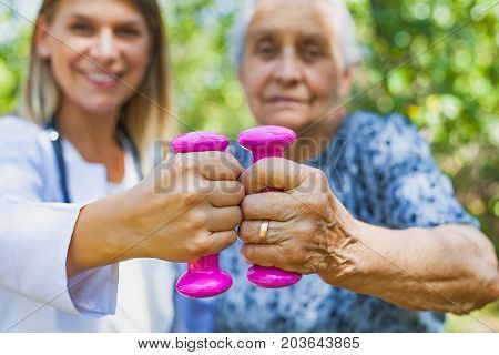 Elderly female doing exercises with dumbbells in the park assisted by young female physician